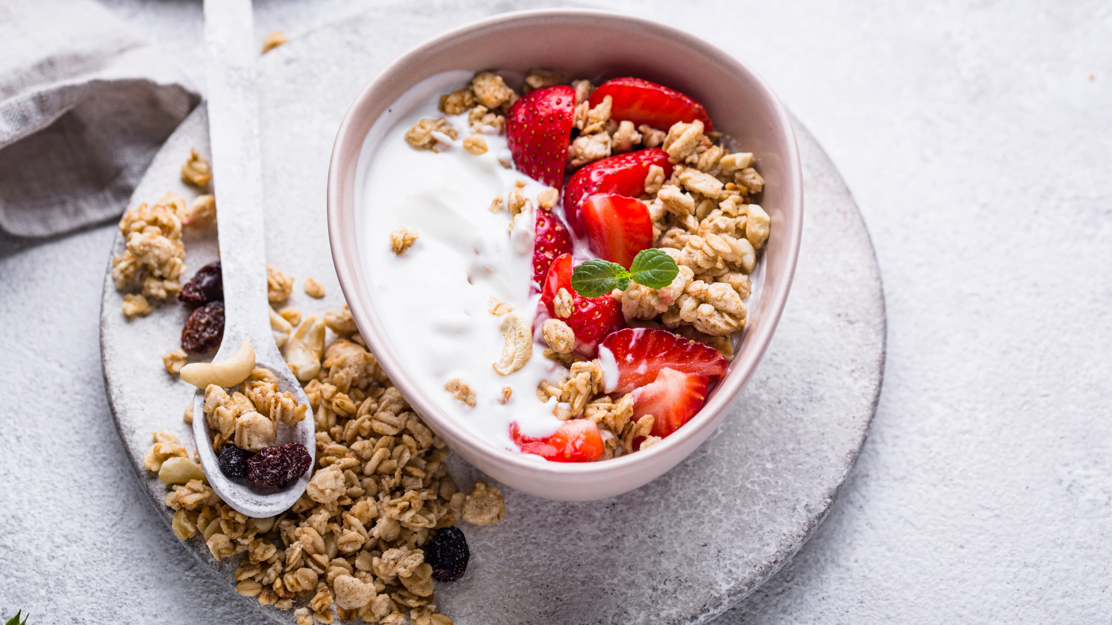 a bowl of greek yoghurt and granola with strawberries