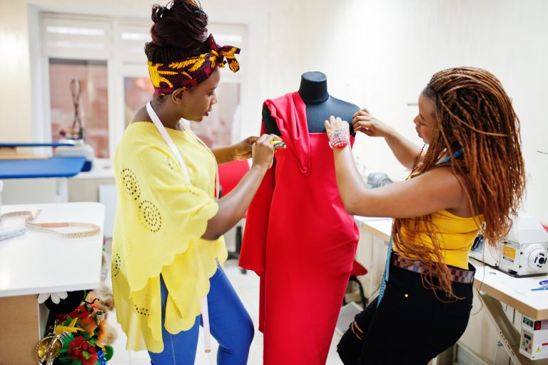 African fashion designer with her client looking over a dress