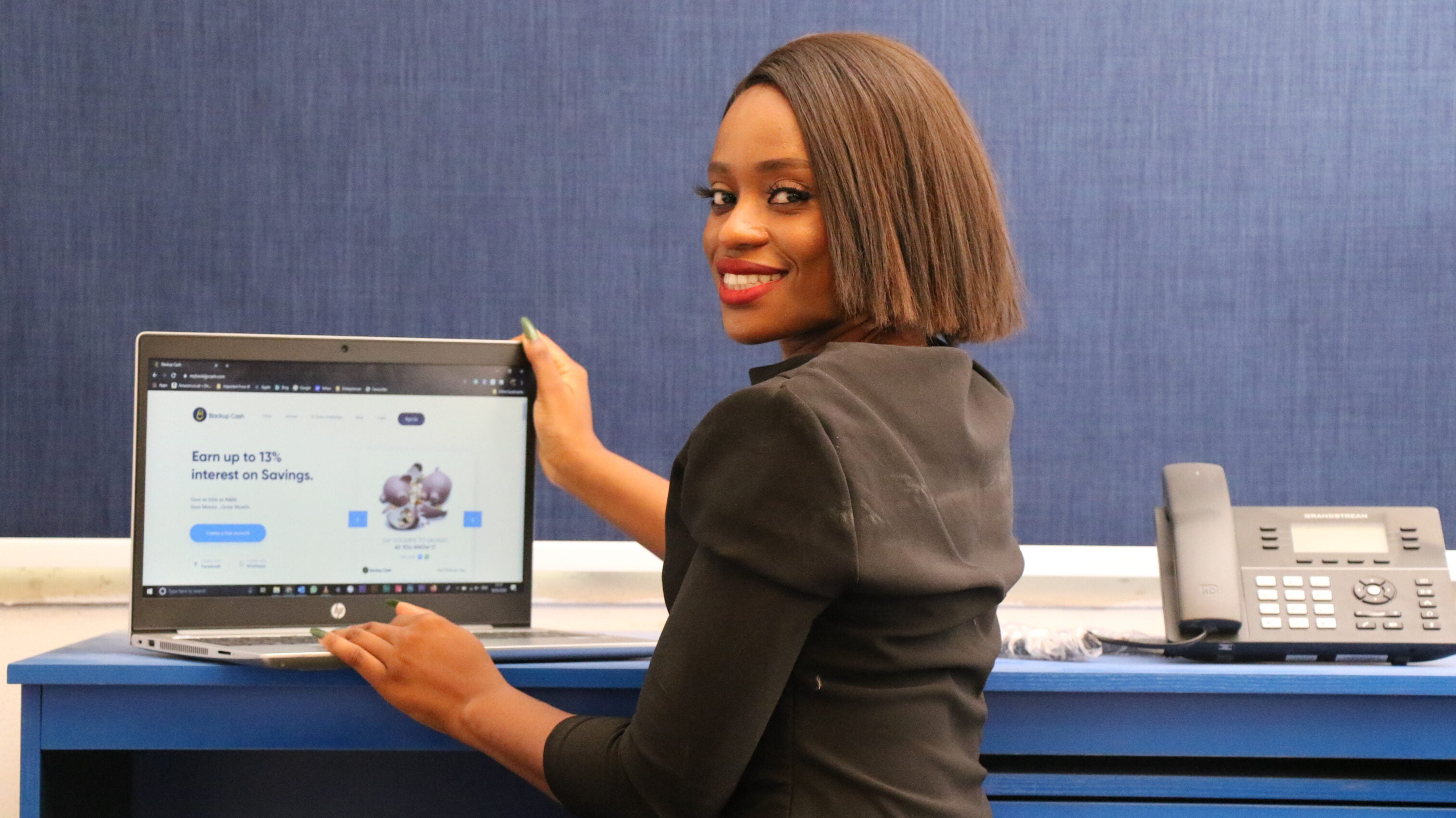 african woman in a corporate dress sitting on her desk
