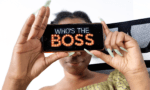 African girl holding a phone with the inscription of Nollywood movie on Netflix, who's the boss- a movie on impostor syndrome