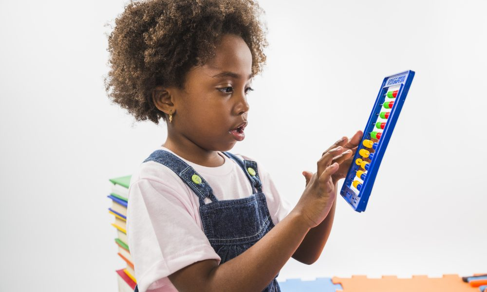 little african girl playing with an abacus game at daycare